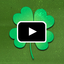 green shamrock in background, video play button in foreground