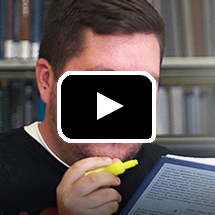 closeup of man holding book and yellow highliter in background, video play button in foreground