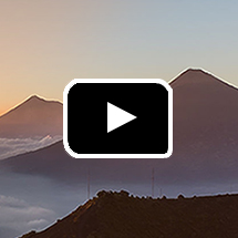 outline of mountains in the distance in background, video play button in foreground