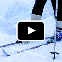 skis, poles, skier's feet in snow in background, video play button in foreground