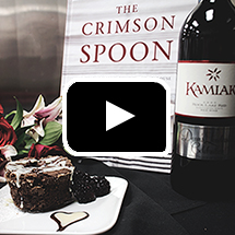 Crimson Spoon cookbook, chocolate cake with berries, wine bottle, flowers, in background, video play button in foreground