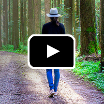 back view of person in hat walking down wooded lane in background, video play button in foreground