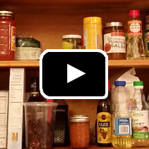food on pantry shelves in background, video play button in foreground