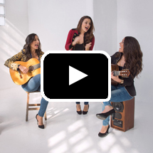 Three women - Las Migas - singing, two play guitars, in background, play button in foreground