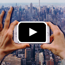 hands taking photo of city skyline with phone in background, play button in foreground