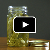 Opened glass pickle jar in background, play button in foreground