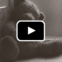sepia-toned teddy bear slumped in corner in background, play button in foreground