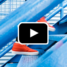 feet in orange sneakers going up stairs in background, play button in foreground