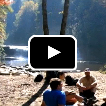 people sitting next to river under trees in background, playbutton in foreground