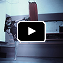 Photo: Young woman kicking a heavy bag in background, play button in foreground.