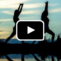 Photo: Two female silhouettes in yoga poses at beach in background, play button in foreground.