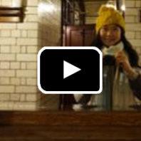 Photo: Woman in knit hat takes selfie in industrial bathroom mirror.