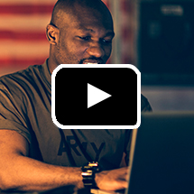 Photo: Army veteran in green Army T-shirt works at laptop in background, play button in foreground.