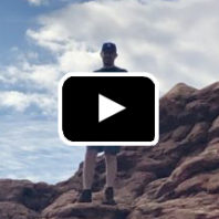 Photo: Man standing on rocks in background, play button in foreground.