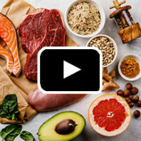 Photo: Overhead view of raw foods - salmon, beef steak, black eyed peas, grapefruit, avocado - in background, play button in foreground.