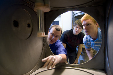 Ron Bliesner (center) examines the cryogenic chamber in Dr. Leachman's (left) lab.