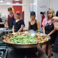 Study abroad students in Spain combining the ingredients for a batch of paella.