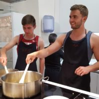 Study abroad students in Spain cooking components for use in a batch of paella.