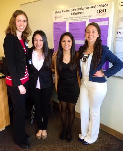 Four female McNair Scholars pose in front of presentation poster