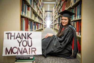 "Graduating Scholar sitting in library with sign that says ""thank you McNair"""