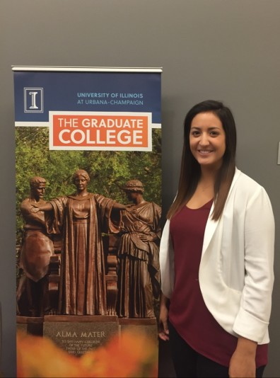 Woman stands beside poster for the University of Illonois' Graduate College