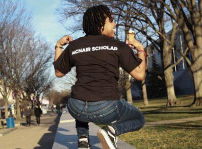 Kelly McNair Scholar power-posing in summer backdrop