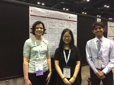 Three people smiling in front of a research poster