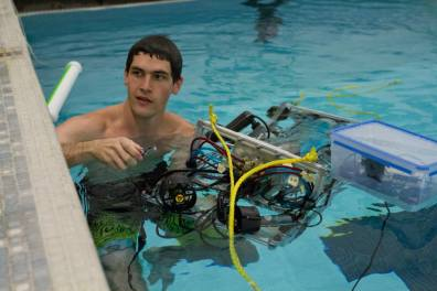WSU student in a swimming pool with RoboSub at a competition