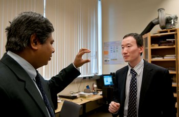 Dr. Dutta and Dr. Liu examining a glass slide used in microfluidics.