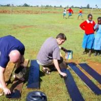 Graduate student Scott Jones painting wood boards to be used to make chimneys in East Africa