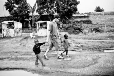 Washington State Architecture student walks hand in hand with children in East Africa