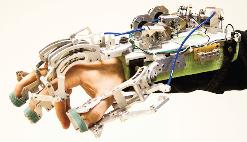 Hakan Gurocak wearing a haptic glove designed using patented technology, including electronically controlled brakes and an actuator.