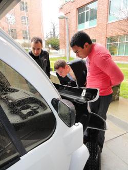 WSU students looking at solar car