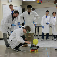 Students wearing safety gear looking at a chemical car that incorporates a yellow balloon.