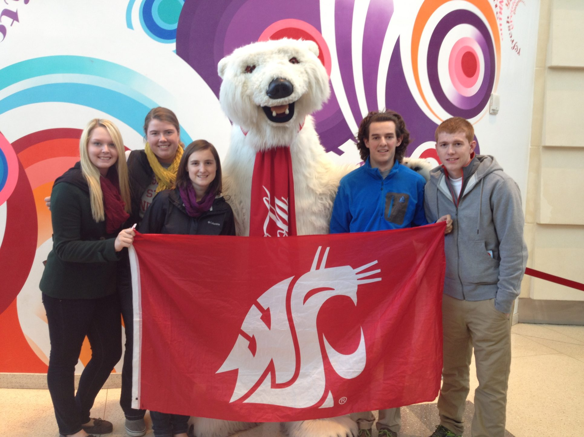 Five students and the Coca-Cola bear mascot pose holding a WSU Cougar flag.
