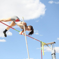 Action shot of Kelsey Bueno clearing the bar during a pole vault.