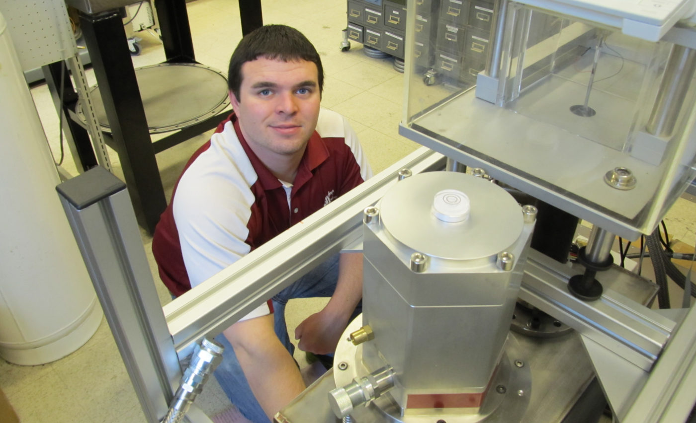 Ian Richardson kneeling by equipment in the research lab.