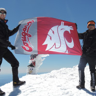 Behrang Asgharian and Jamie Adams on top of Mount Adams holding WSU flag.