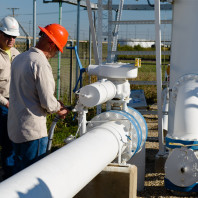 Two men at a pipeline measuring methane.