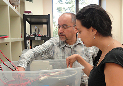 Haluk Beyenal and a grad student work with a fuel cell.