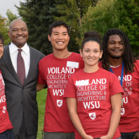 Four Voiland College students wearing crimson t-shirts pose with WSU president Elson S. Floyd.