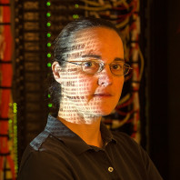Jennifer Adam in the Information Technology Building Server room with data projected on her face.