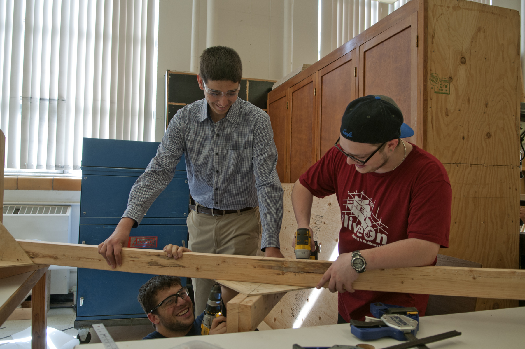 Three students working together to build a large wood frame.