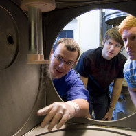 Three people looking through a circular opening into a cryogenic chamber.