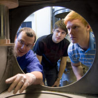 Ron Bliesner (center) examines the cryogenic chamber in Dr. Leachman's (left) lab at Washington State University in the Voiland College of Engineering and Architecture.