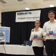 Bailee and Mitchell pose next to their product display.