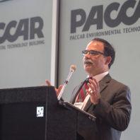 """Dan Bernardo at a podium with a wall displaying """"PACCAR Environmental Technology Building"""" behind him."""