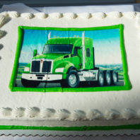 White sheet cake with a photo of a green Kenworth truck on it.