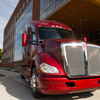 Red PACCAR Kenworth truck parked in front of the new PACCAR Environmental Technology Building.