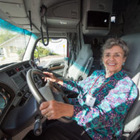 Woman seated at the steering wheel inside a PACCAR truck.